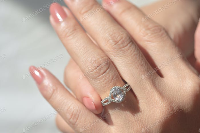 Close-up view of diamond ring and woman hand