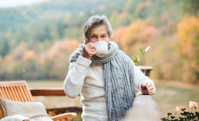 An elderly woman drinking coffee outdoors on a terrace in autumn.