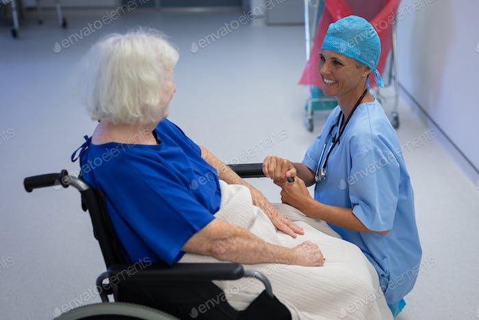 Weiblicher Chirurg im Gespräch mit älteren weiblichen Patienten sitzen in einem Rollstuhl im Krankenhauskorridor