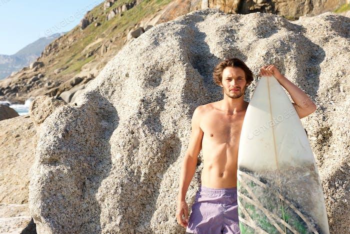Hombre guapo posando con tabla de surf en el Playa