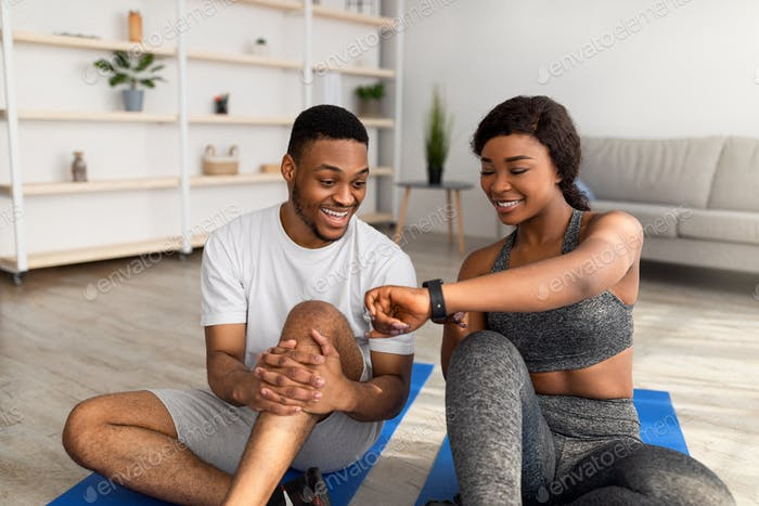 Sporty black lady showing data on smartwatch or fitness tracker to her boyfriend after home workout