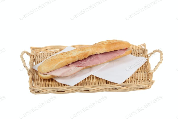 Simple ham baguette on a wicker tray