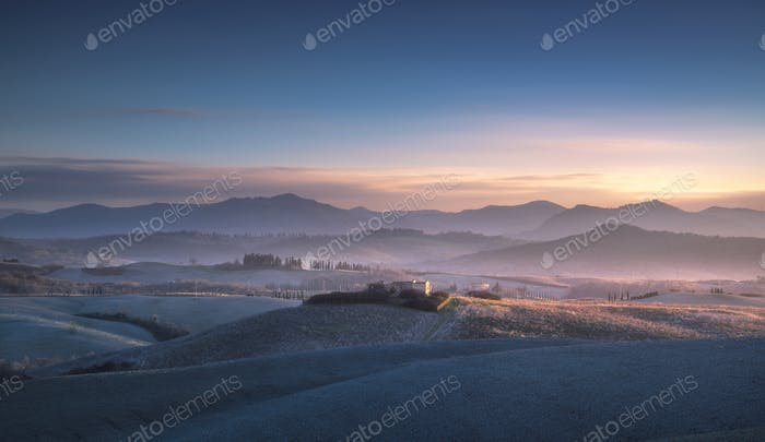 Volterra winter panorama, rolling hills and fields on blue sunse