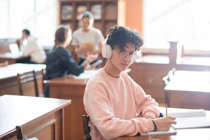 Youthful clever student of college looking at you through eyeglasses