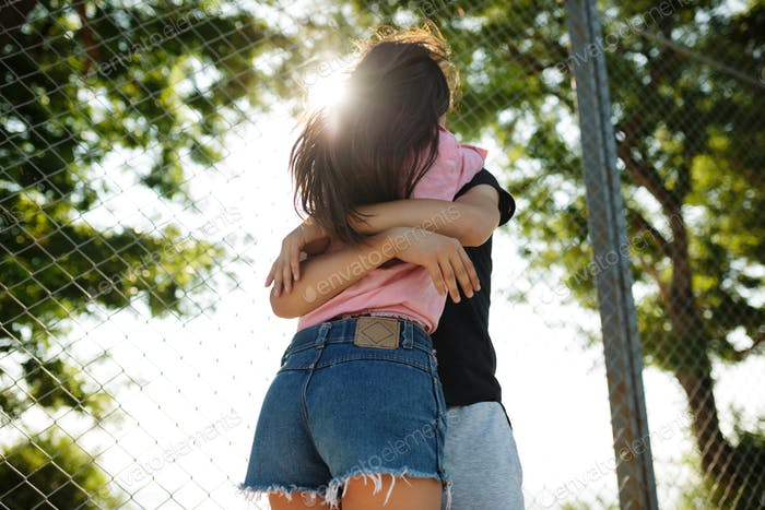 Young beautiful couple standing and embracing one another in park