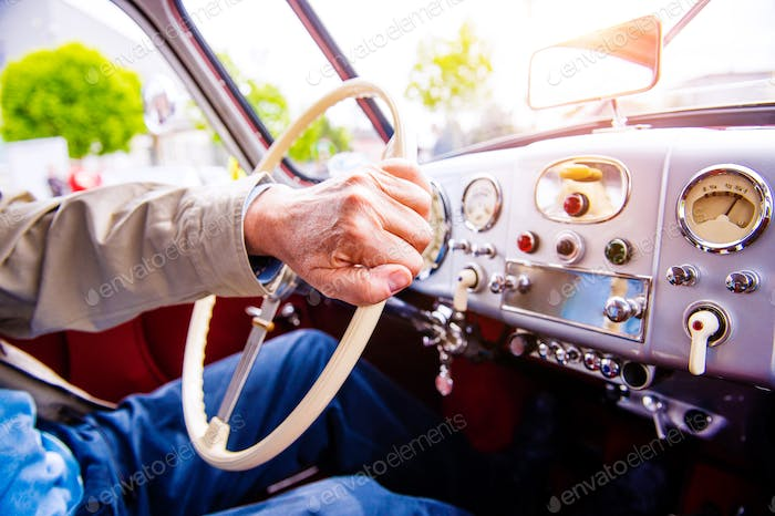 Close up unrecognizable man driving a veteran car