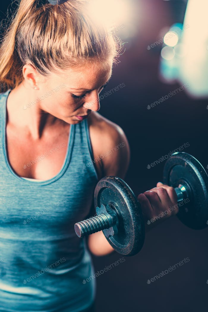 Female athlete exercising with dumbbells
