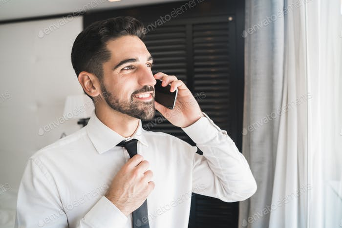 Businessman talking on the phone at the hotel room.
