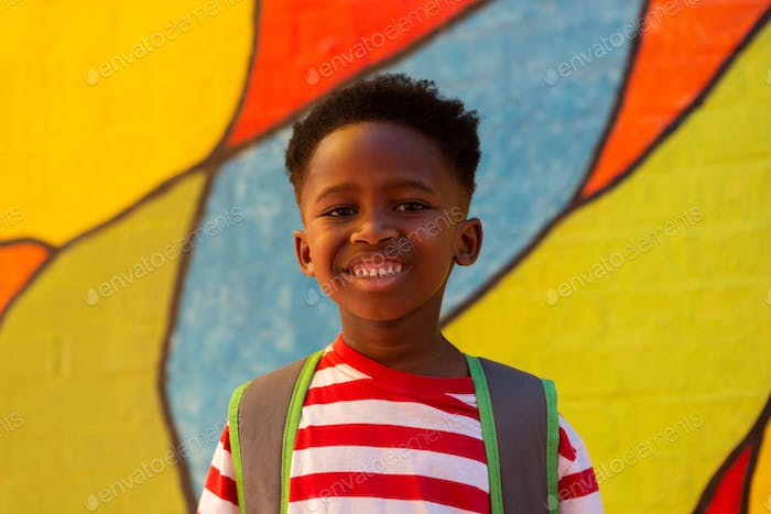 Portrait of a happy African American schoolboy standing in the school playground
