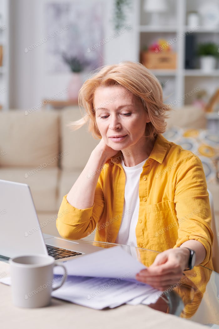 Mature blond businesswoman in smart casualwear looking through papers