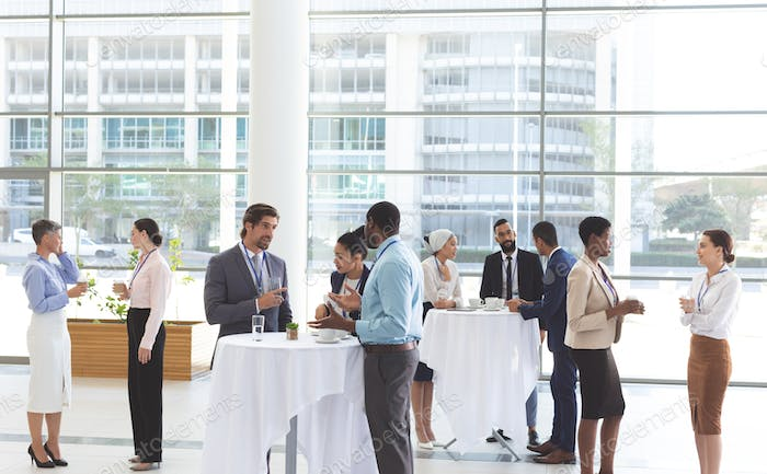 Diverse business people interacting with each other at table after a conference in office lobby