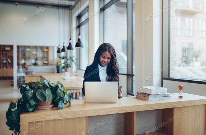 Smiling African American businesswoman busy working at her office desk