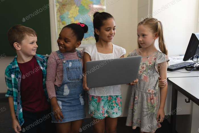 Group of happy schoolkids standing with digital tablet in classroom