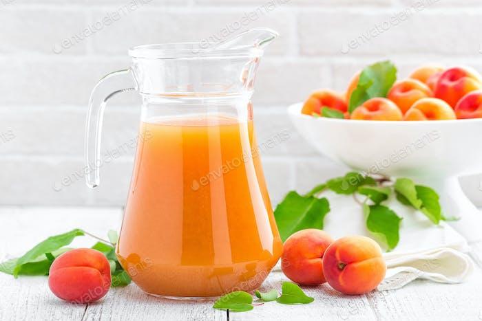 Aprikosensaft und frische Früchte mit Blättern auf weißem Holztisch