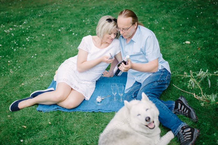 Middle age couple with their pet at picnic