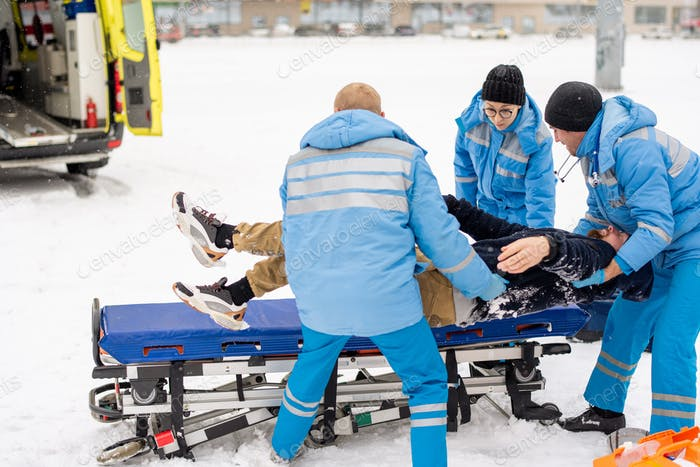 Brigade of paramedics in winter uniform putting unconscious man on stretcher