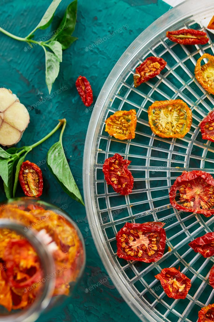 Homemade sun dried tomatoes with herbs, on the sieve from dryer.