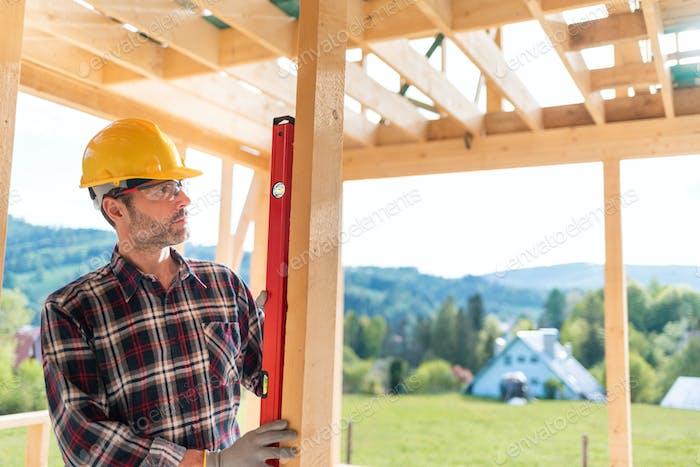 Arbeiter mit Arbeitswerkzeugen, die an der Baustruktur auf der Baustelle arbeiten