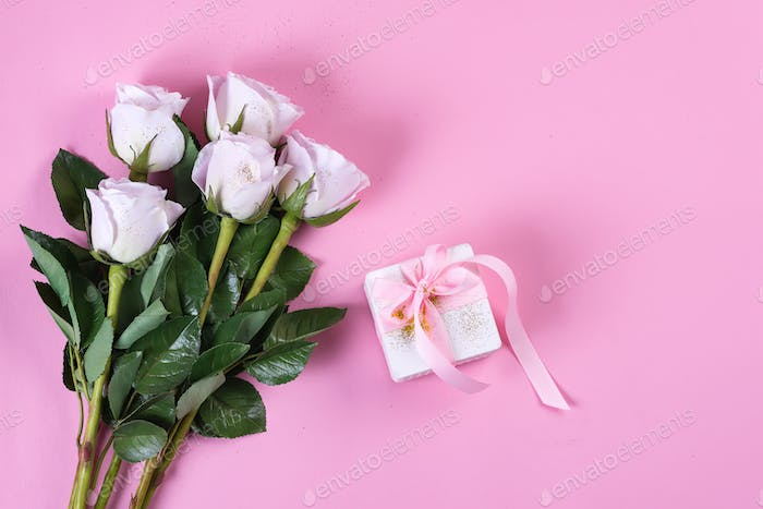 Pink rose and white gift box with pink ribbon on pink background