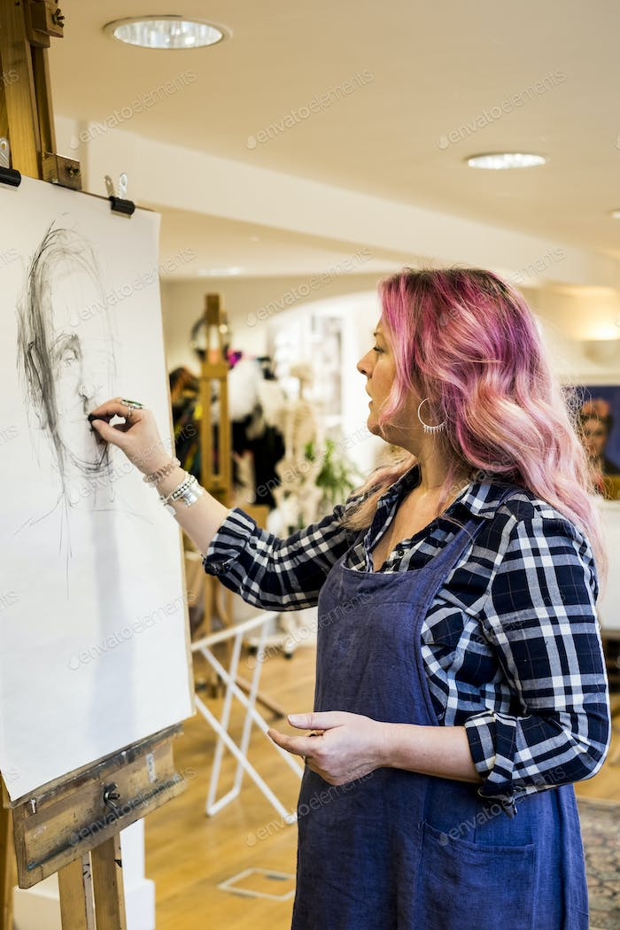 Woman with long blond wavy hair with pink streaks wearing apron standing at an easel, drawing a