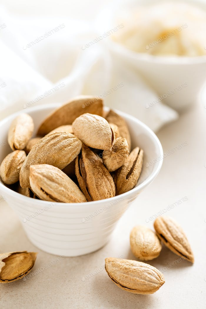 Almond nuts in a bowl on white background, healthy eating
