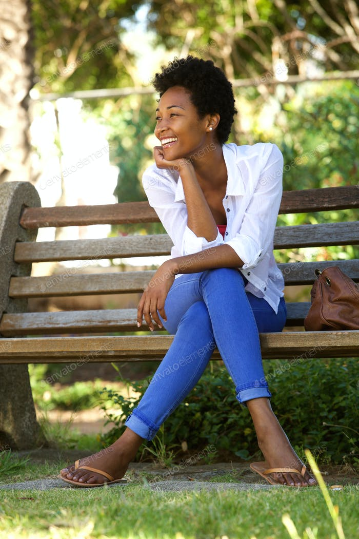 Young african woman sitting relaxed on a park bench