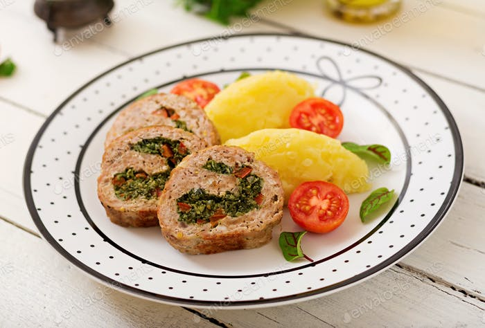 Roll of turkey minced meat with spinach and red sweet pepper with garnish of mashed potatoes