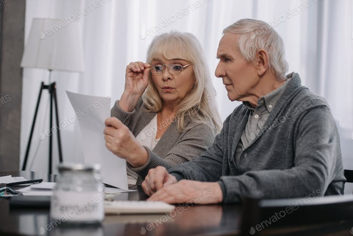 surprised senior couple sitting at table and looking at bills