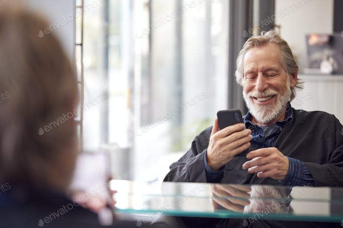 Senior Man Waiting To Have Hair Cut In Hairdressing Salon Looking At Mobile Phone