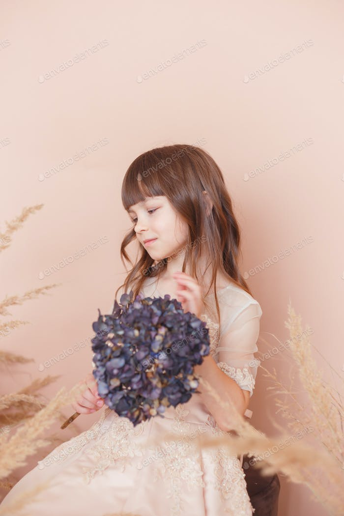 Young model girl in beige dress with lilac branch. Soft color portrait. Studio shot