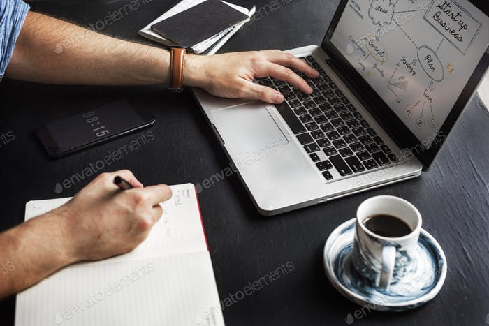 Man Hand Writing Startup Business Note from Laptop