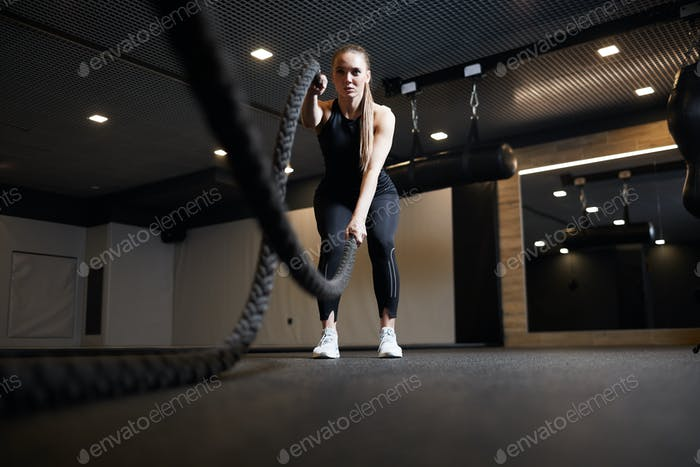Focused Young Woman Working Out with Battle Ropes
