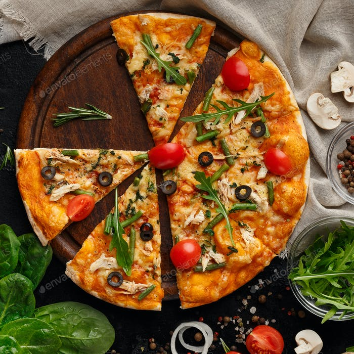 Sliced pizza with tomatoes and herbs on cutting board