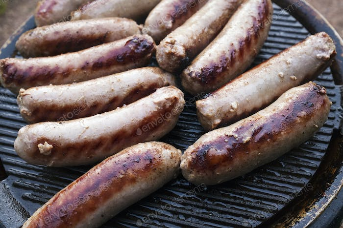 Sausages arranged on top of a barbeque grill, cooking outdoors.
