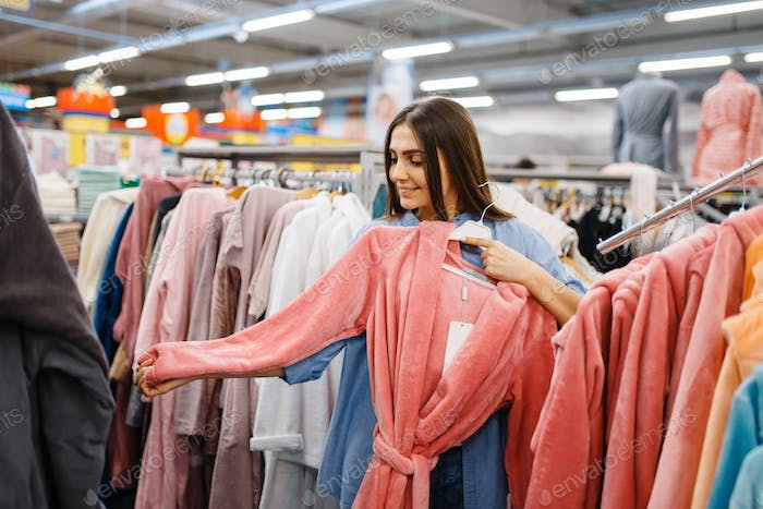Young woman choosing bathrobe in bed linen store