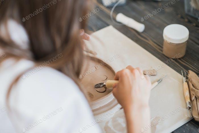 Nahaufnahme eines Meisters Töpfer, Ton Schneiden Spezialwerkzeug. Künstlerin schneidet mit einer hölzernen Schleife