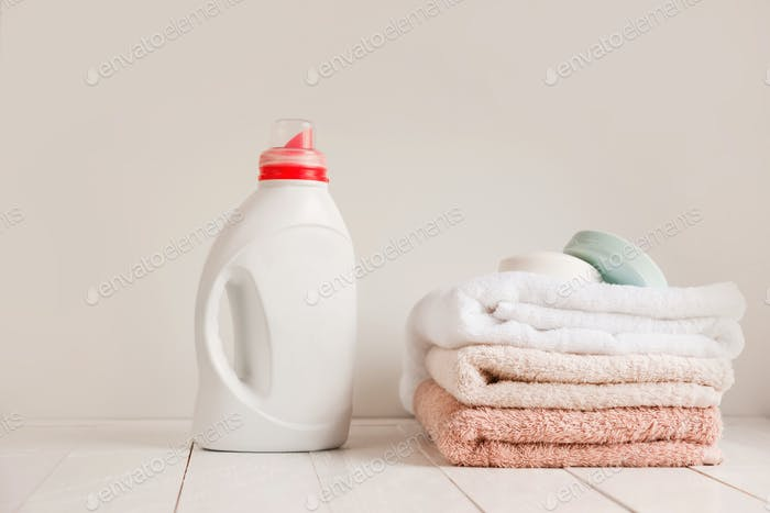 A stack of clean towels after washing and a white bottle with gel for linen