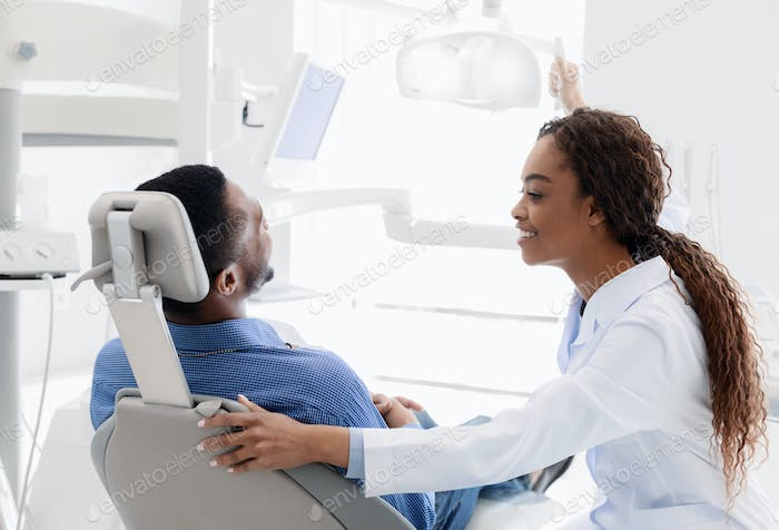 Black lady stomatologist greeting man at clinic
