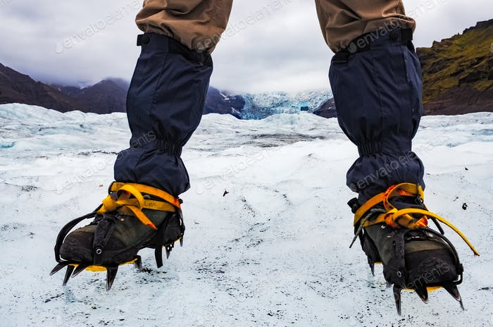 Mountaineer's feet with crampons on the frozen glacier, Vatnajokull