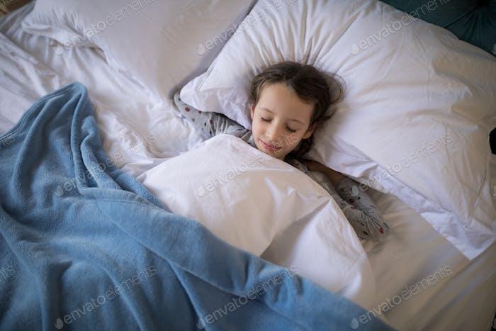 Girl sleeping on bed in bedroom