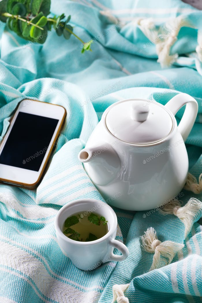 Cup of tea and cell phone in a bed with a teapot on a blue plaid