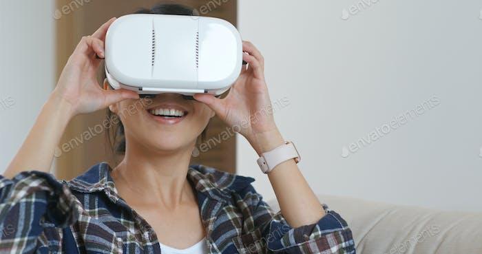 Frau beobachten, obwohl Virtual Reality Gerät zu Hause