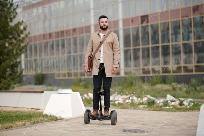 Contemporary young elegant businessman riding gyroscope outdoors