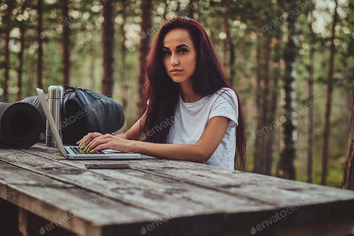 Cheerful student is working on the laptop in the middle of the forest.