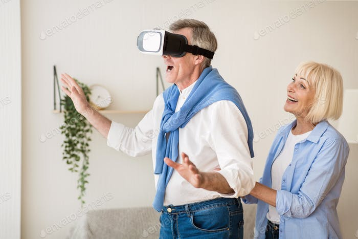 New feelings. Excited mature man using the VR glasses