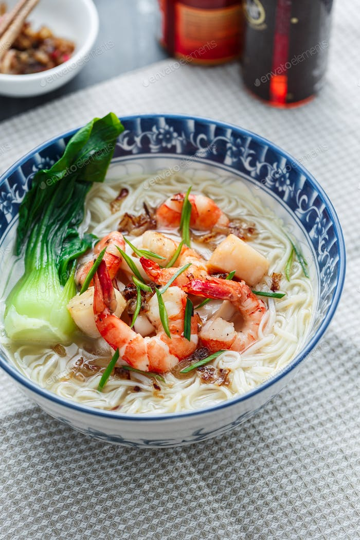 Bee hoon soup bai me fen or noodle soup with seafood and chicken broth, close view