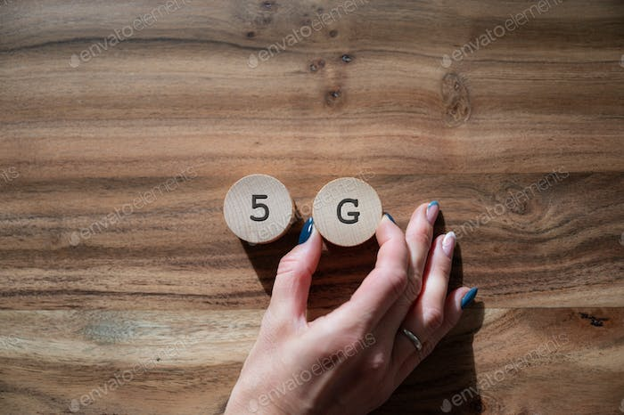 Placing two wooden cut circles spelling 5G on a desk