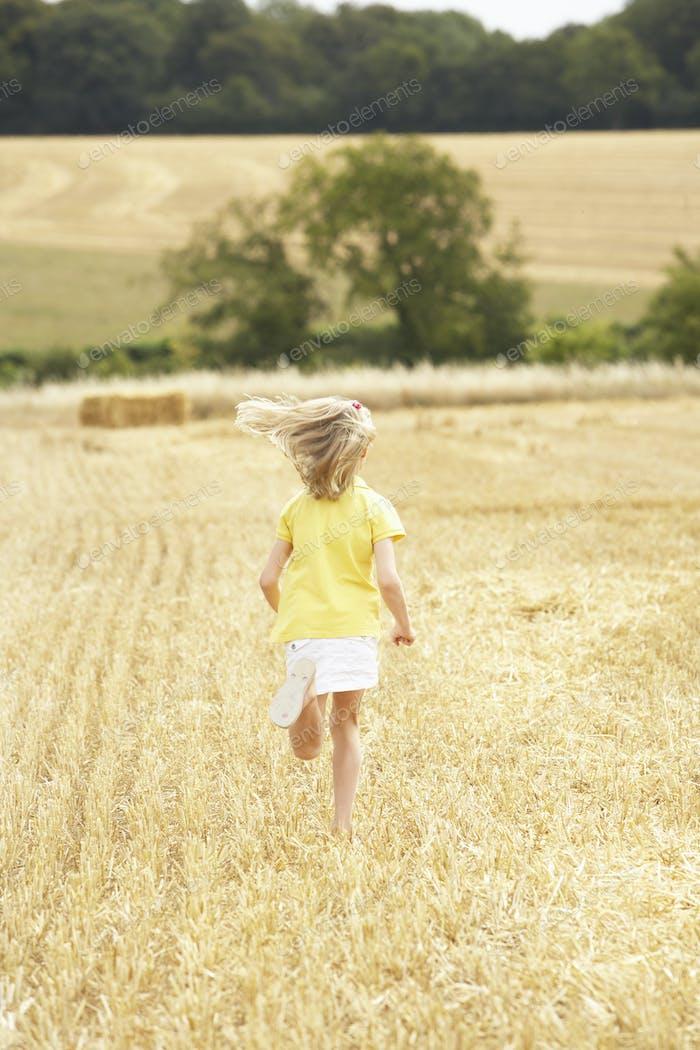 Girl Running Through Summer Harvested Field