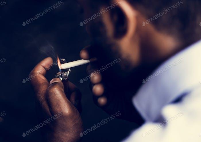 Rückansicht des Menschen, der eine Zigarette anzündet