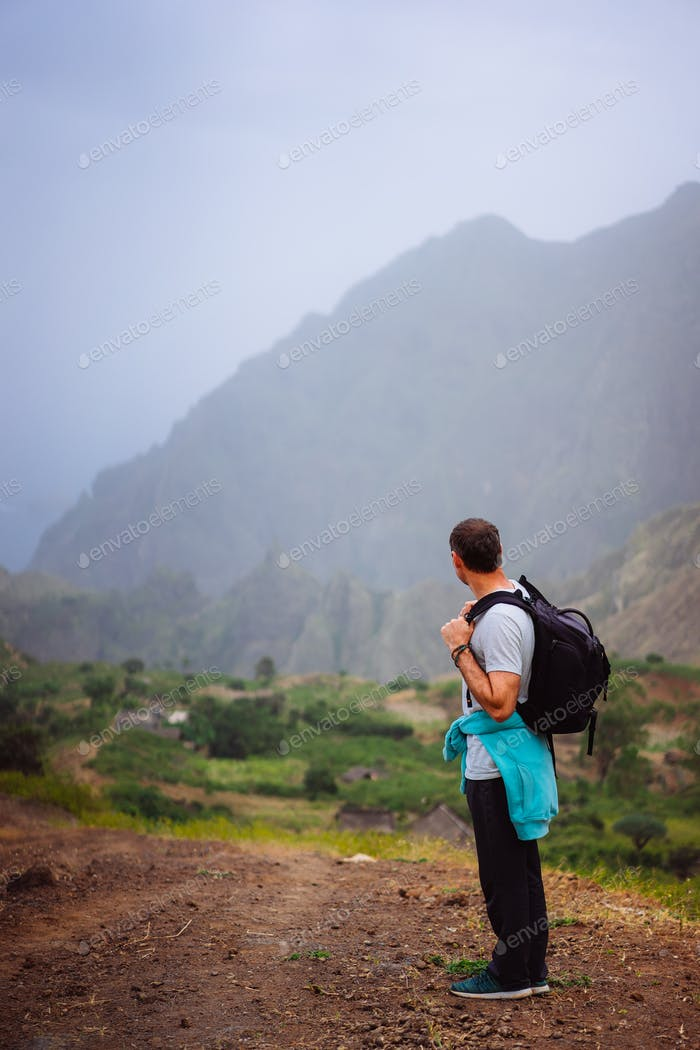 Hiker with backpack in arid terrain in front of a incredible panorama view of high mountain ranges